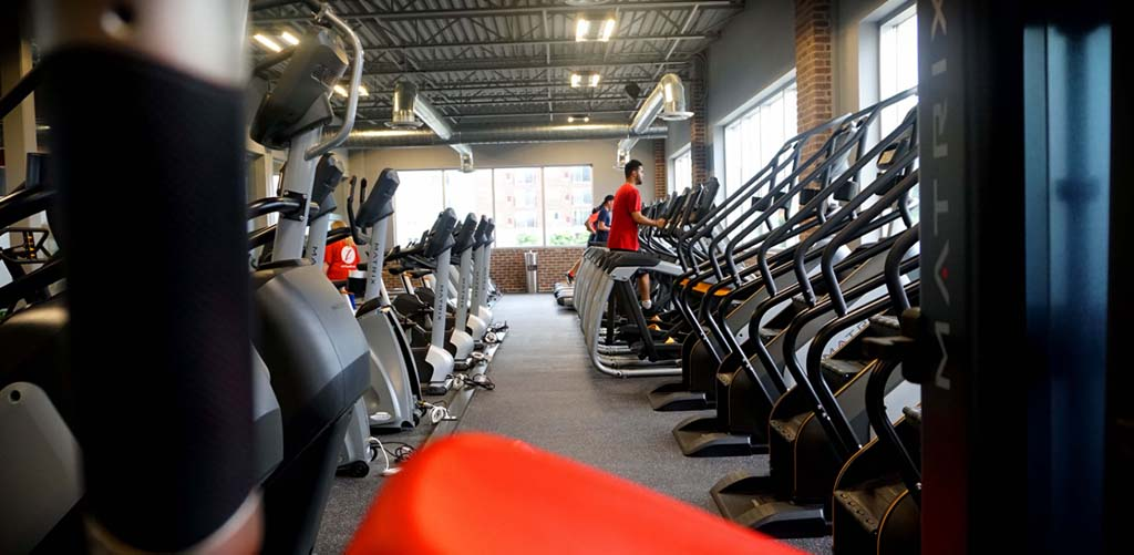 cardio training equipment in gym with fitness members on treadmills