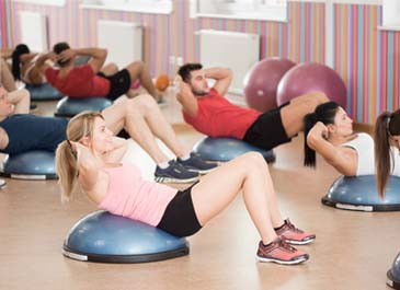 group fitness class doing sit ups on gym equipment