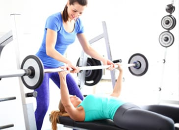 woman on fitness bench bench pressing while personal trainer assisted