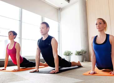 gym members doing yoga in group fitness class