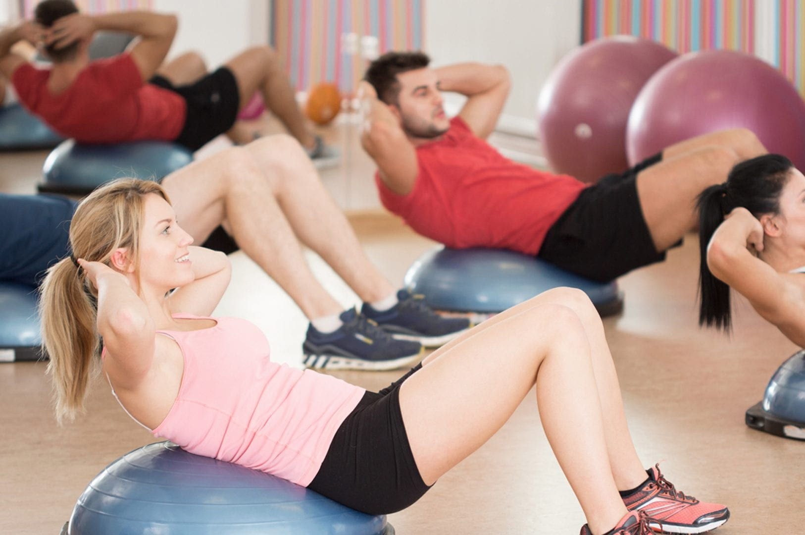 group fitness classes exercising in gym studio