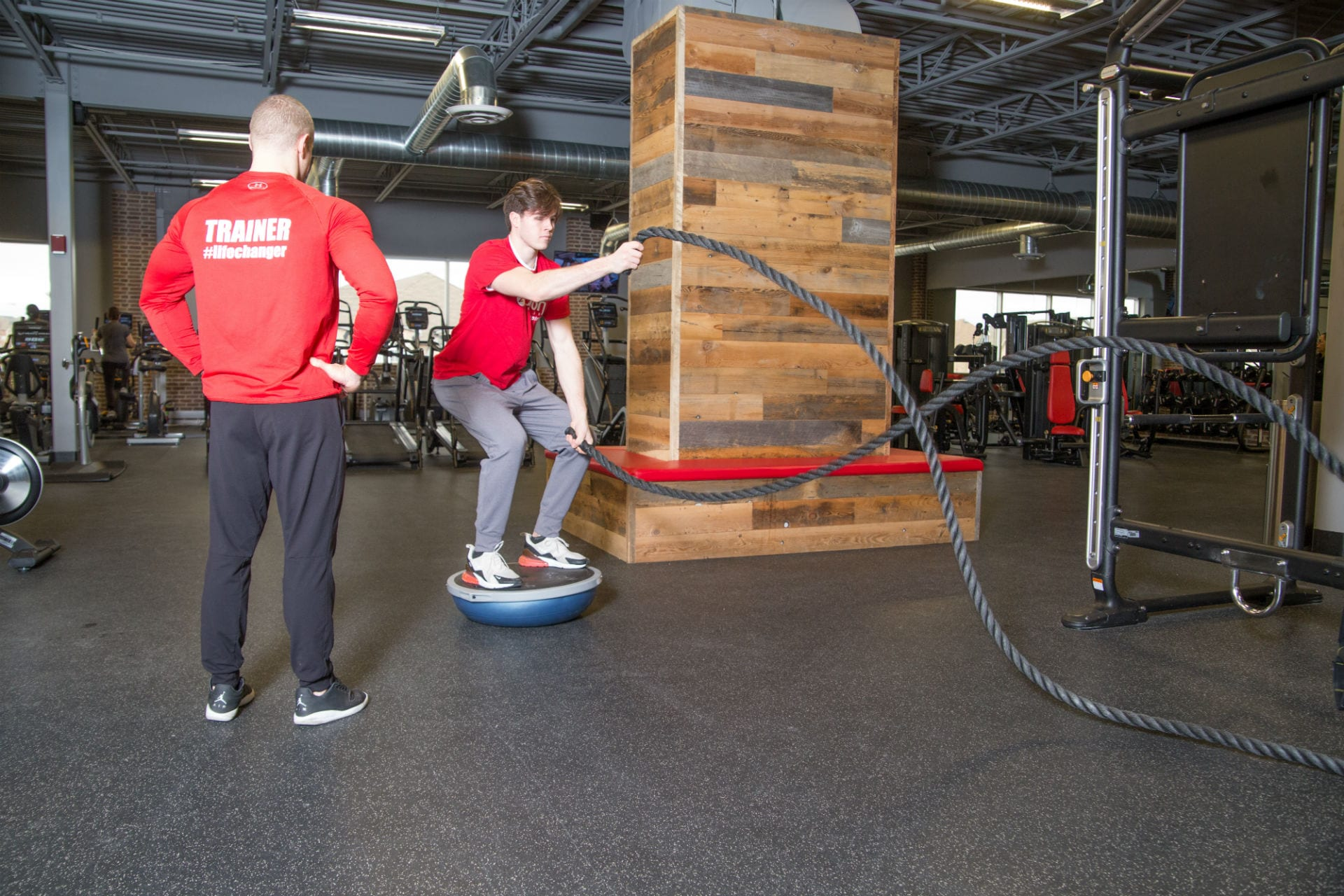 gym personal trainer coaching gym member using functional ropes