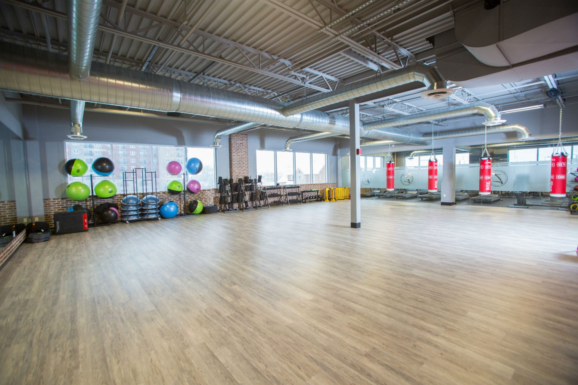 gym studio with fitness equipment around the perimeter with large windows overlooking city