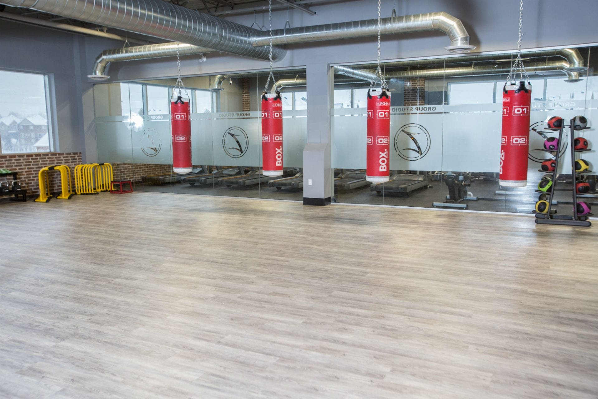 boxing bags and fitness equipment around perimeter of industrial modern gym studio