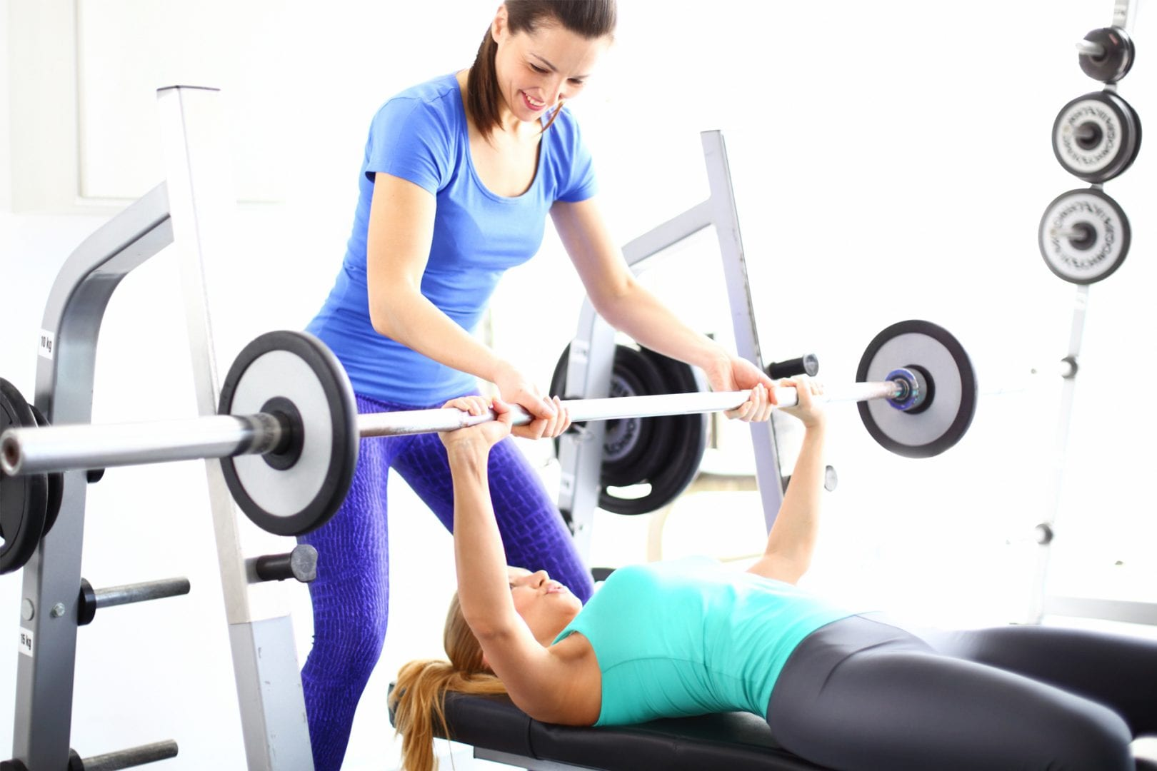 personal-trainer-assisting-female-gym-member-bench-press-at-fitness-center