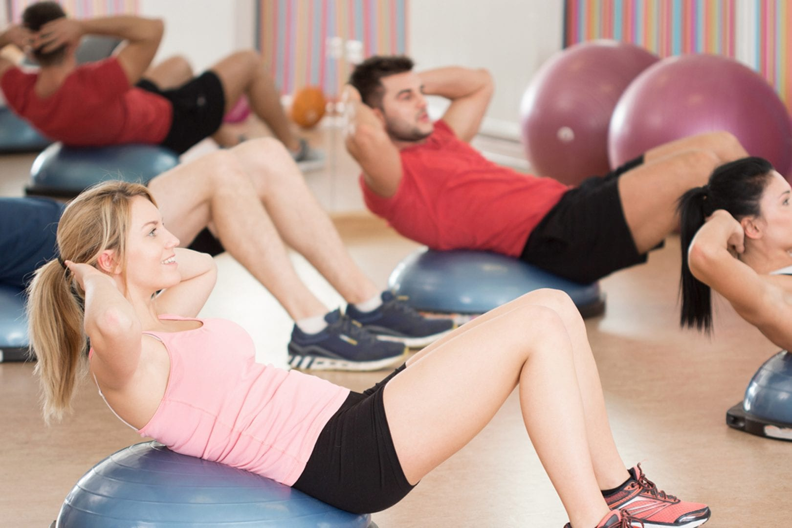 gym-members-in-group-cardio-classes-laying-on-gym-balls-doing-sit-ups-in-fitness-center-studio