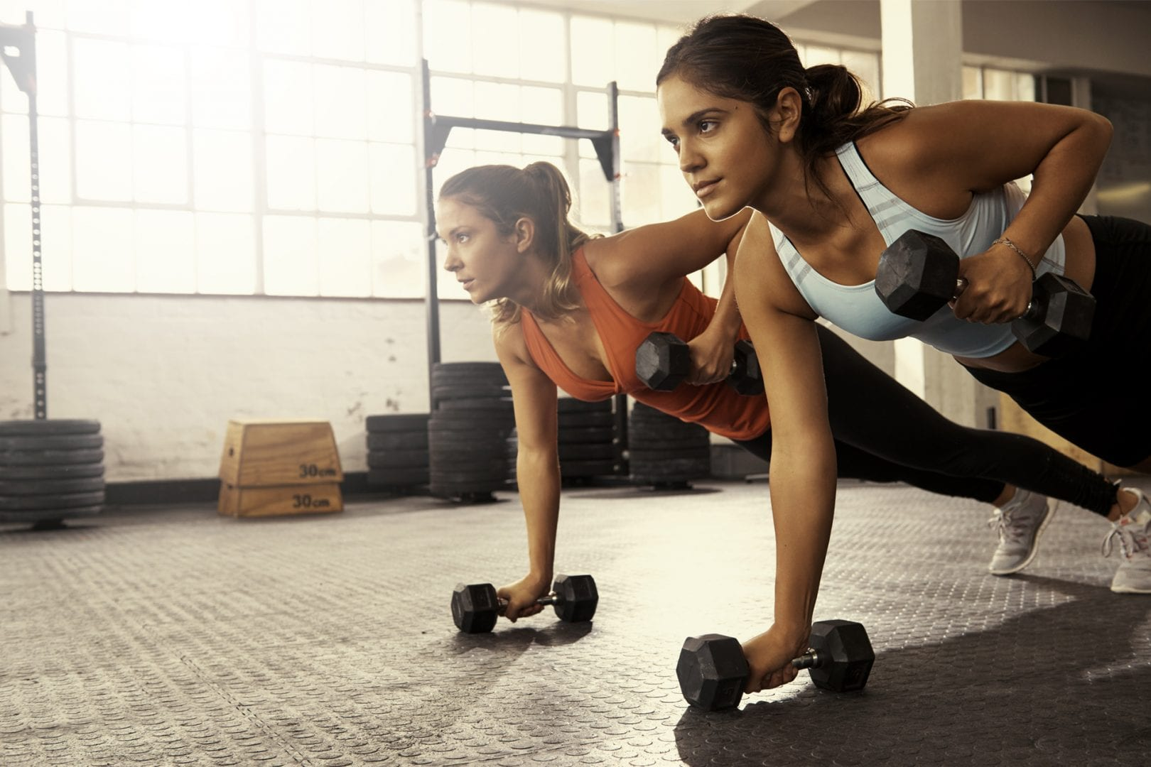 two-women-on-gym-floor-holding-weights-doing-pull-ups-in-fitness-center