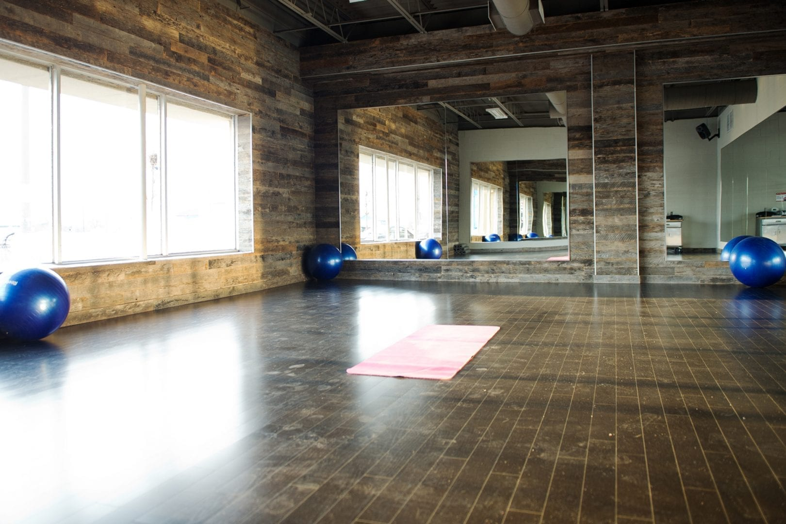 group-fitness-studio-with-glass-windows-mirrors-and-wood-shiplap-walls-and-floors